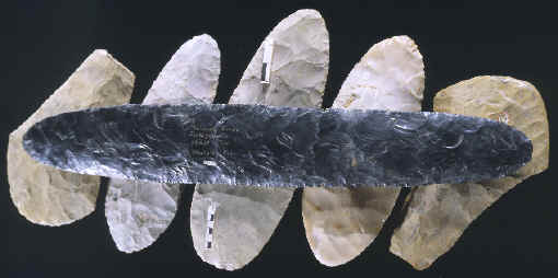 Large obsidian biface laying on 5 large spades.